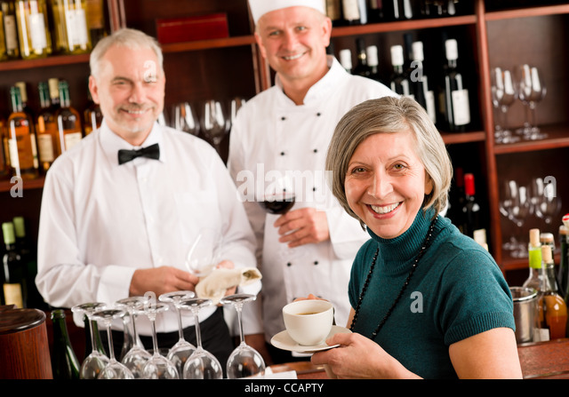Restaurant smiling manager have break with staff wine bar - Stock Image