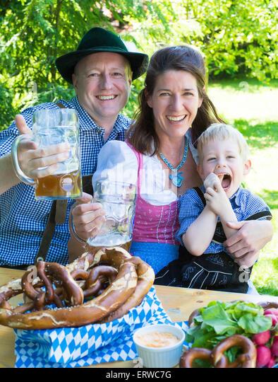 bavarian family sitting outside on a bench and smiling - Stock-Bilder