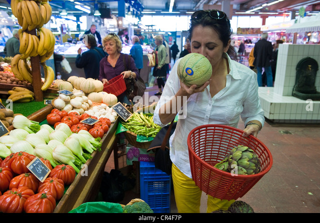 France, Herault, Sete, covered market of the Halles, buyer of melons on a fruits and vegetables stand - Stock Image