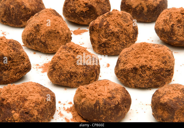 Bunch of chocolate truffles with cocoa powder on a white surface - Stock Image