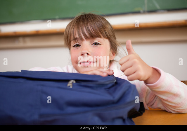 Schoolgirl posing with a bag and the thumb up - Stock Image