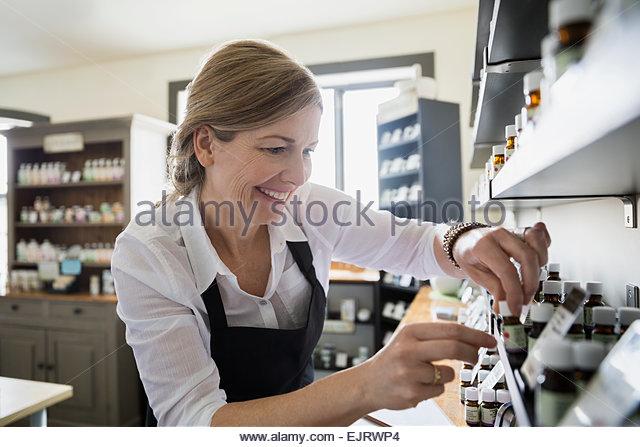 Apothecary shop owner arranging bottles on shelf - Stock Image