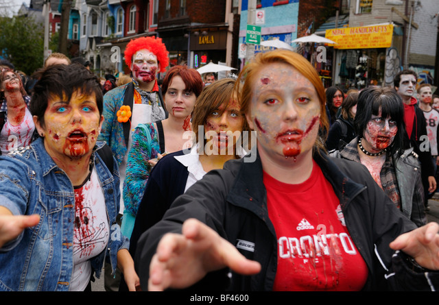 Mob of made up bloody Zombies play acting by reaching for victims while lurching along in the annual Toronto walk - Stock Image