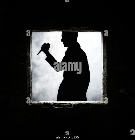 a man with a knife at a window of an old, abandoned house - Stock Image