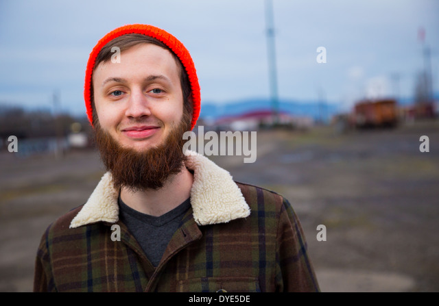 Modern, trendy, hipster guy in an abandoned train yard at dusk in this fashion style portrait. - Stock Image