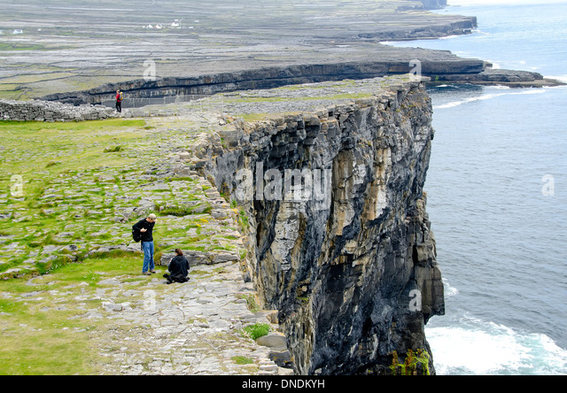 Tourists at steep cliff beside Dun Aengus prehistoric stone fort, Inishmore (Inis Mor), Aran Islands Ireland - Stock Image