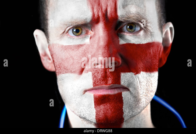 Aggresive football fan with their face painted with the English flag. - Stock Image