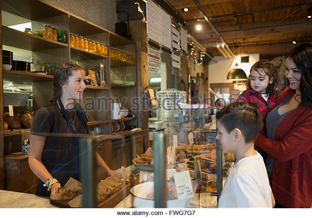 Bakery worker serving family - Stock Image