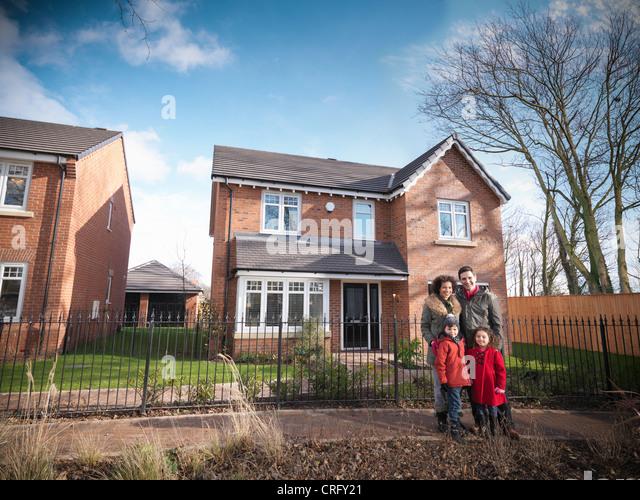 Family smiling outside house - Stock Image