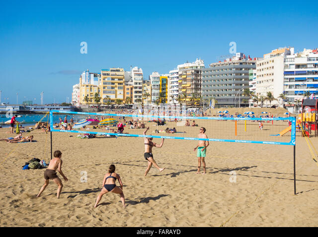 Young people playing Volleyball on Las Canteras beach in Las Palmas, Gran Canaria, Canary Islands, Spain - Stock Image