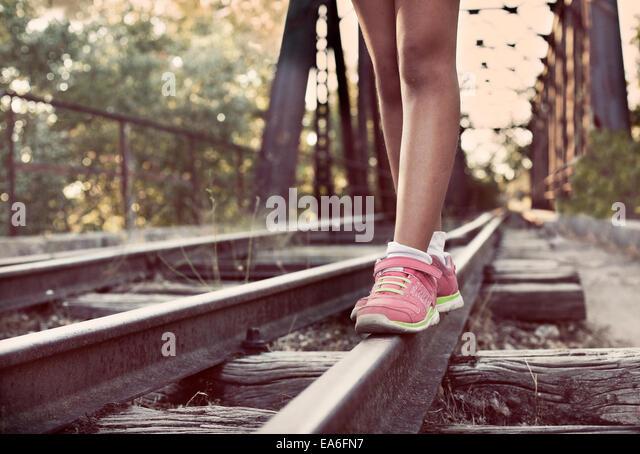 Close-up of woman's legs walking along train tracks - Stock Image