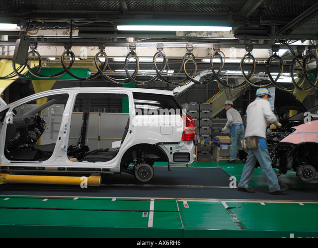 Factory workers producing the hybrid Toyota Prius cars work on the assembly line at the Toyota City - Stock Image