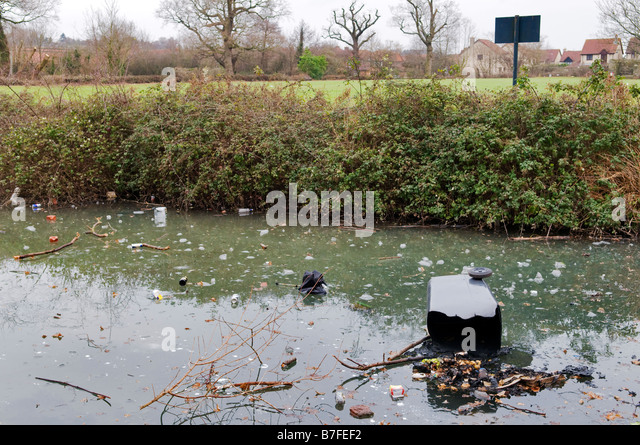 General rubbish and a refuse collection wheelie bin full of rubbish thats been dumped on a frozen local duck pond - Stock Image