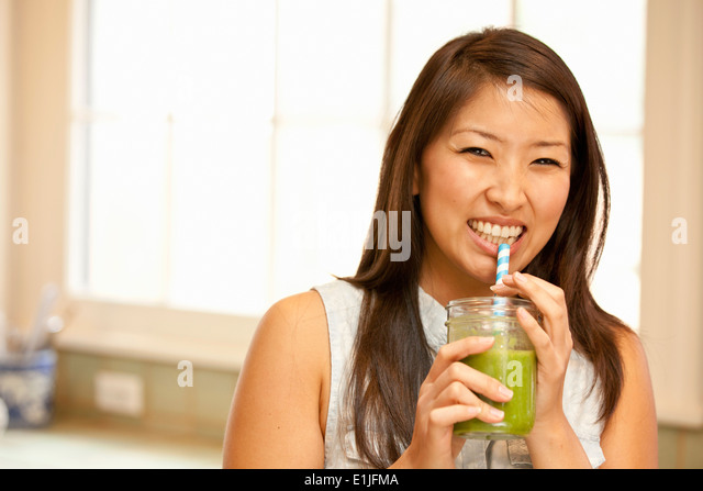 Young woman sipping green smoothie - Stock Image