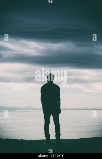 Man standing by the river - Stock Image