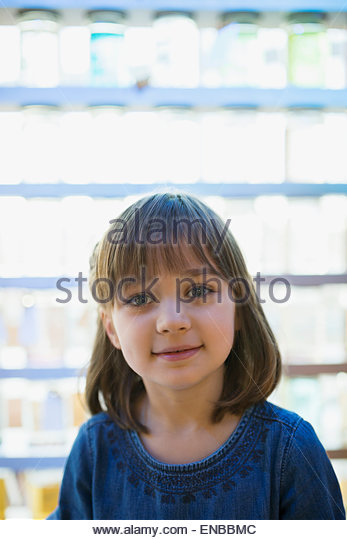 Portrait smiling girl in front of backlit jars - Stock Image