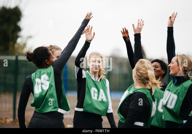 Female netball team giving high fives on netball court - Stock Image