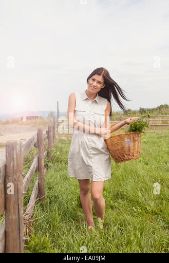 Young woman with basket of vegetable on field, Roznov, Czech Republic - Stock-Bilder