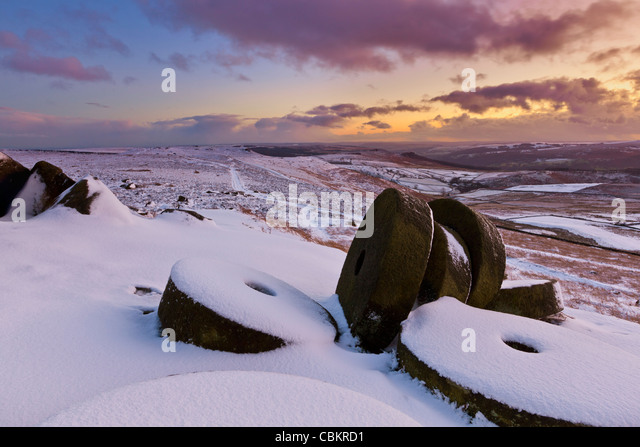 Millstones in snow at Sunset on Stanage Edge, Peak District National Park, Derbyshire, England, UK - Stock Image