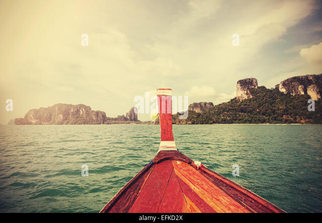 Retro toned wooden boat and a tropical island in distance. - Stock Image
