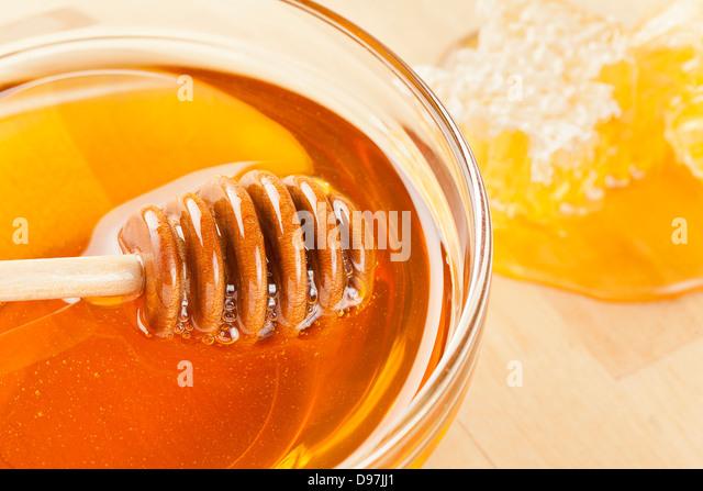 Golden Organic Honey against a back ground - Stock Image