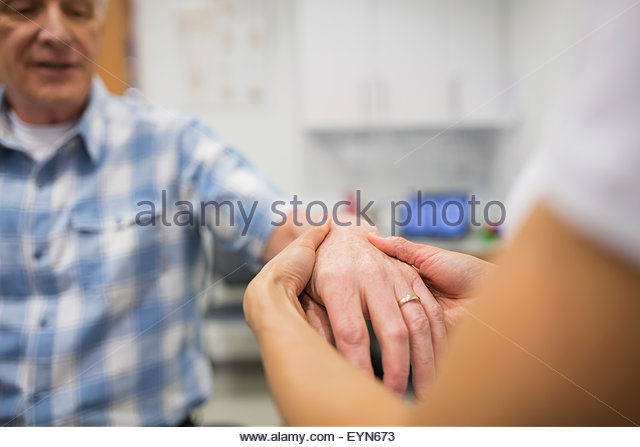 Close up physical therapist feeling patient hand - Stock Image