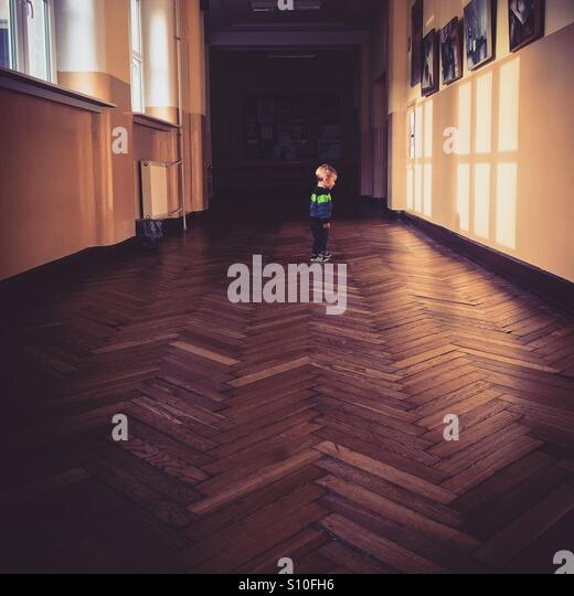 Baby boy standing in a long school hallway looking at shadows - Stock Image