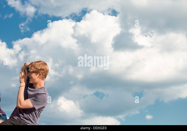 Young man taking photograph with clouds in sky - Stock Image