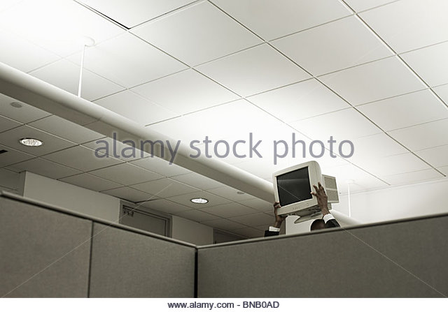 Person holding up computer monitor in office - Stock Image