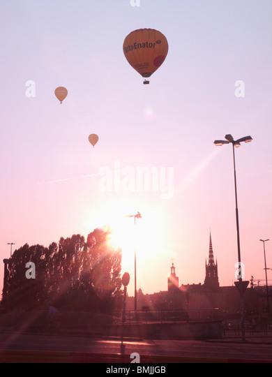 Scandinavia, Sweden, Stockholm, Sodermalm, Slussen, Silhouette of hot air balloons in sky (lens flare) - Stock Image