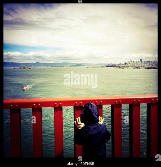A seven year old boy looks at a tourist cruise boat and San Francisco through the rail on the Golden Gate Bridge. - Stock Image
