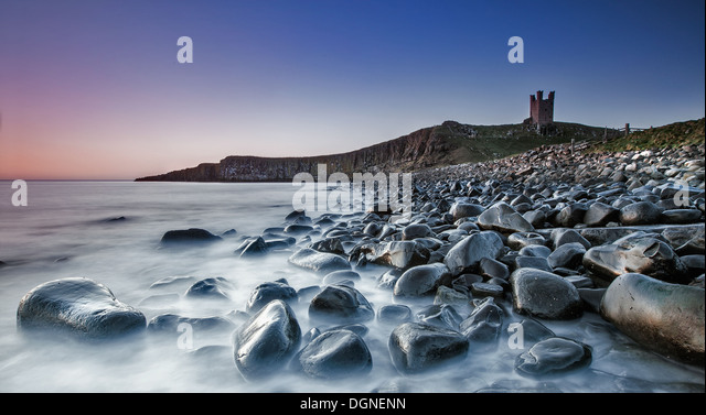 Pebbly beach with castle ruins in the background - Stock Image