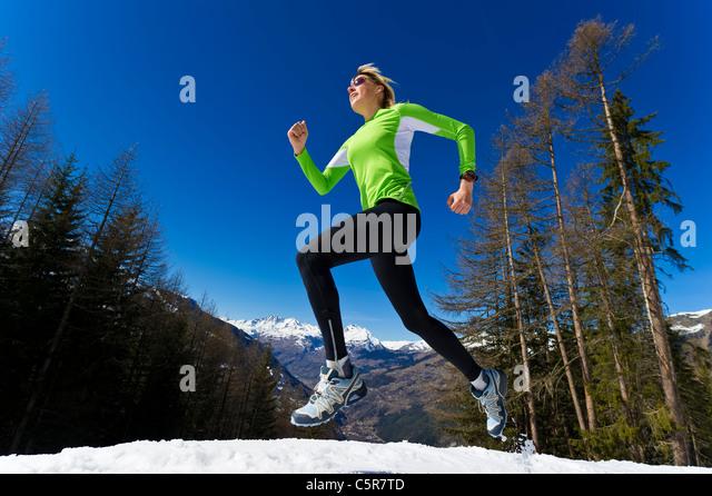 A woman jogging through snowy winter mountains. - Stock-Bilder