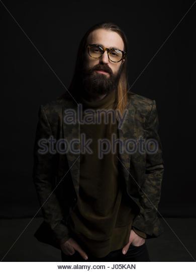 Portrait confident brunette hipster man with beard and eyeglasses against black background - Stock Image