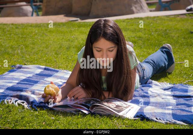 Hispanic/Caucasian girl reading magazine in park. MR  © Myrleen Pearson Pearson - Stock-Bilder