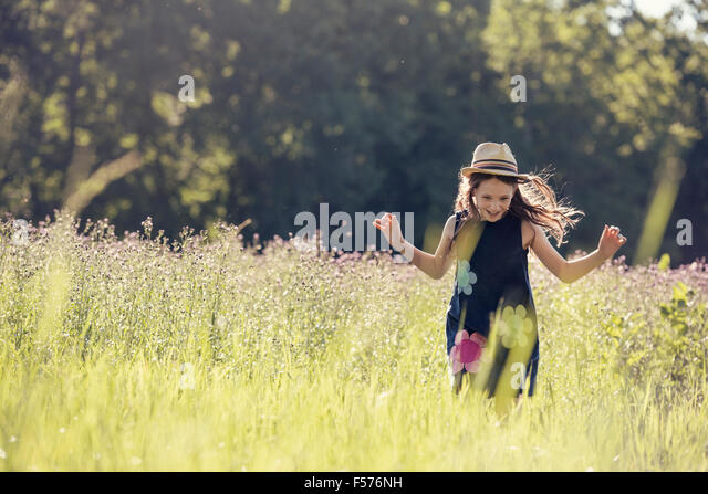 A child, a young girl in straw hat in a meadow of wild flowers in summer. - Stock Image