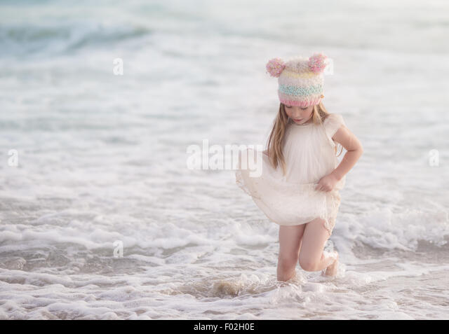 Girl in a dress walking in the ocean - Stock Image