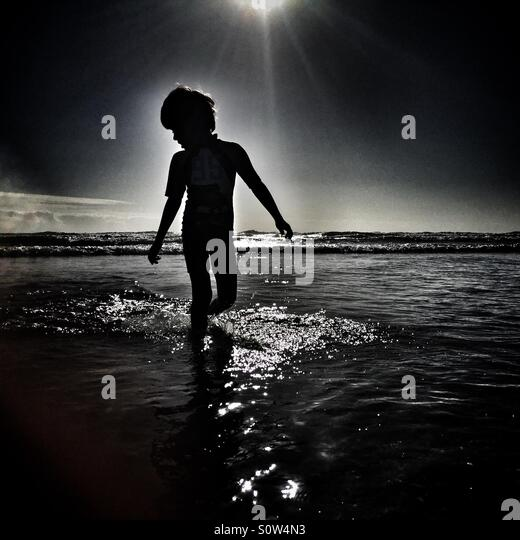 Boy on beach silhouette - Stock Image