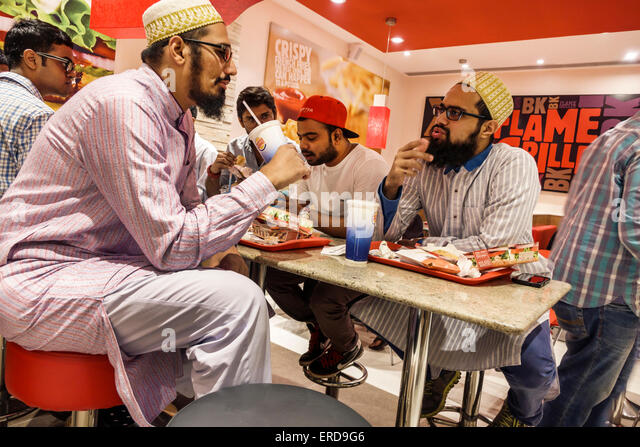 India Asian Mumbai Lower Parel High Street Phoenix mall inside restaurant Burger King fast food man friends sitting - Stock Image