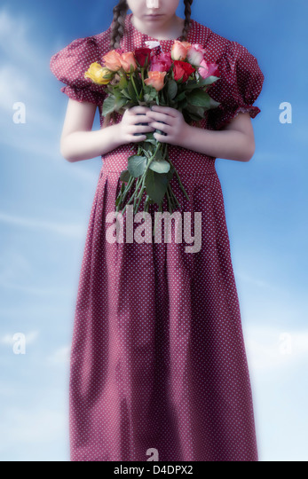 a girl in a red dress holding a bouquet of flowers - Stock Image