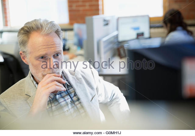 Serious businessman using computer in office - Stock Image