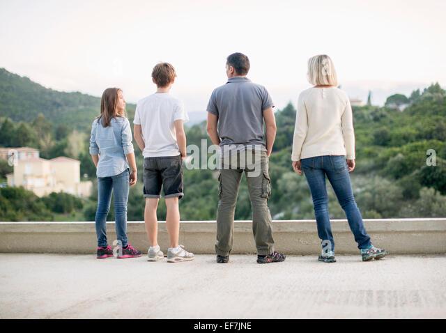 Family standing on terrace - Stock-Bilder