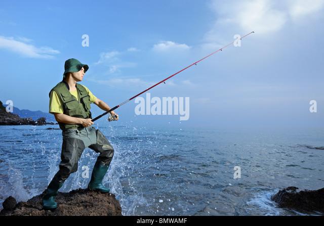 A fisherman fishing at the Ionian sea - Stock Image