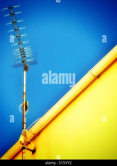 Television aerial on top of yellow wall against a clear blue cloudless sky - Stock-Bilder
