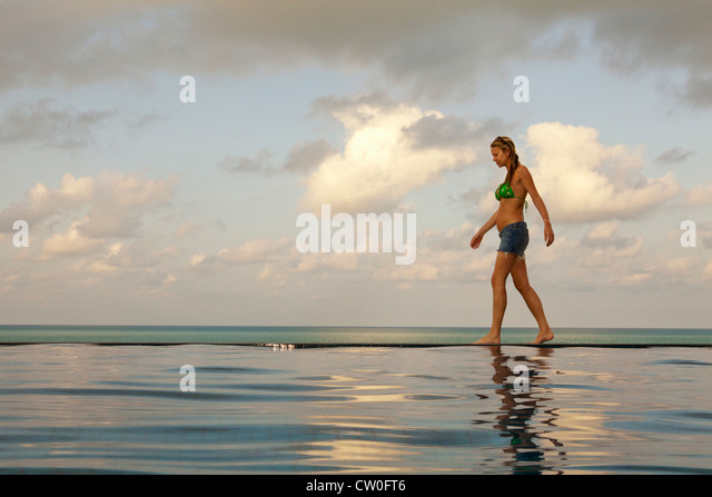 Woman walking at edge of infinity pool - Stock Image