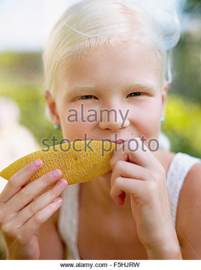 Denmark, Girl (10-11) eating melon - Stock Image