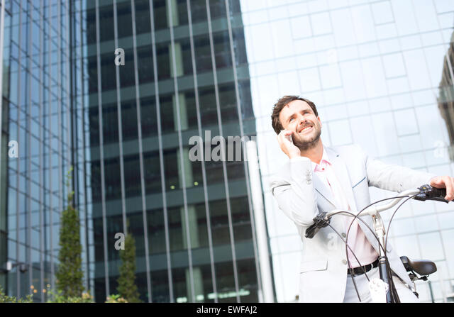 Low angle view of businessman answering mobile phone while sitting on bicycle outdoors - Stock-Bilder