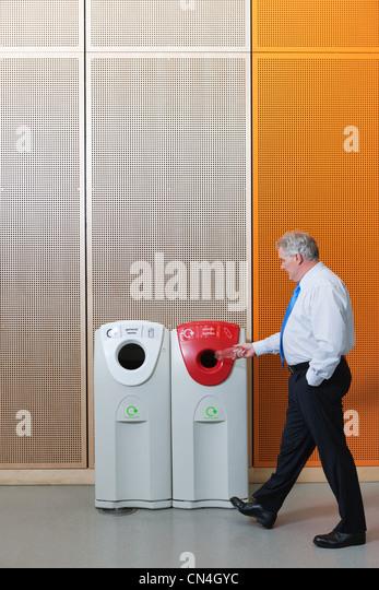 Businesman disposing of bottle in recycling bin - Stock Image