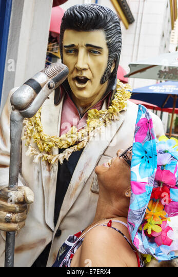 Hawaii Hawaiian Oahu Honolulu Waikiki Beach Kings Village Shopping Center Elvis Presley microphone statue woman - Stock Image