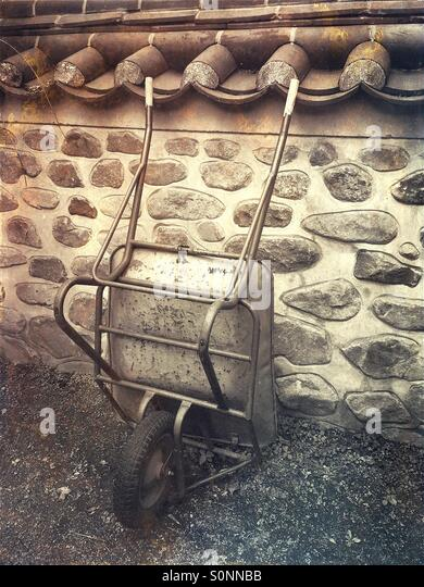 Wheelbarrow leaning on stone wall in sepia tones with rusty, vintage paper texture overlay. - Stock Image